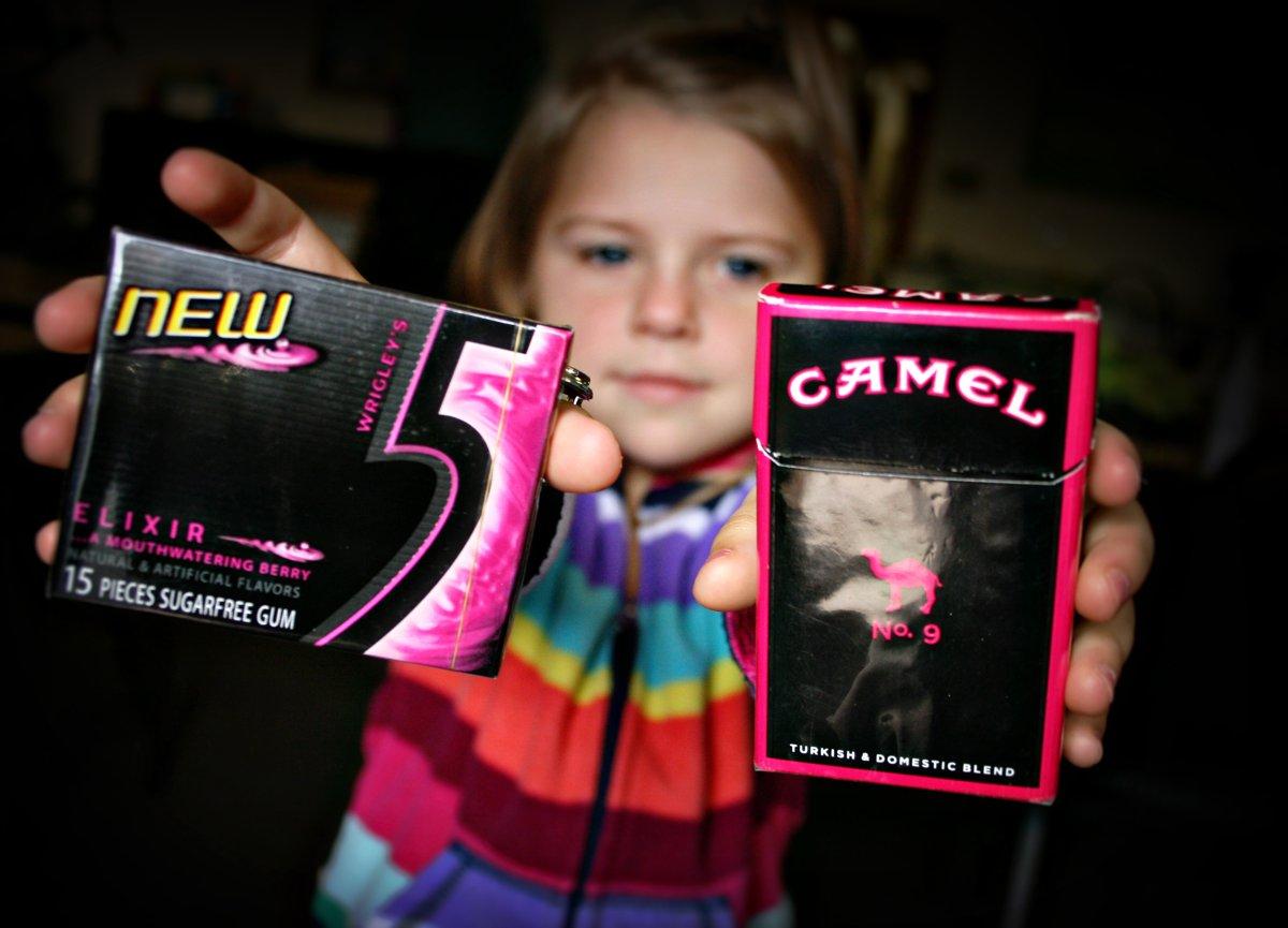 Djevojčica u jednoj ruci drži paklicu žvaka, a u drugoj paklicu cigareta. Može li ona da ih razlikuje?